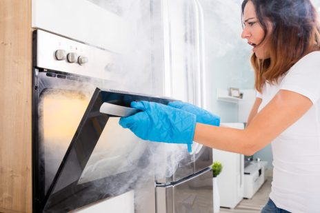 Young Unhappy Woman Opening Door Of Oven With Full Of Smoke